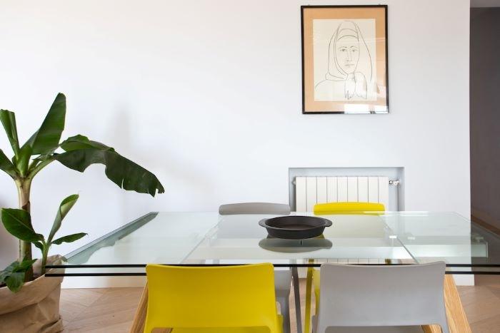 Mesa de salón con sillas amarillas y tono gris en el salón