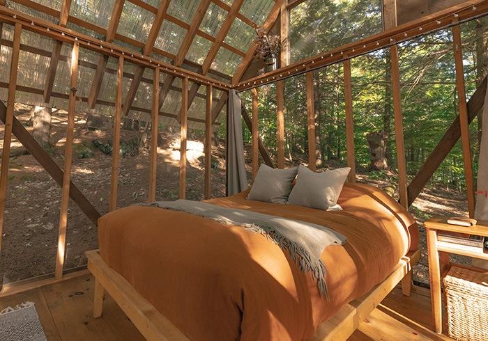 Dormitorio con cama de matrimonio y paredes con cristales transparentes