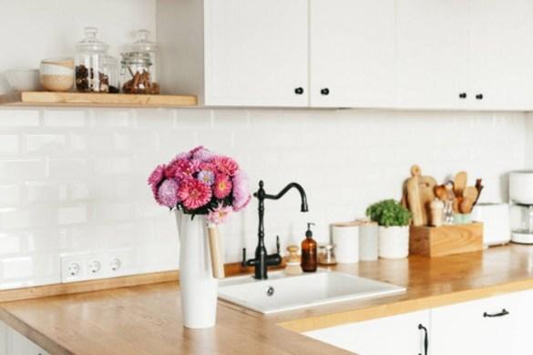 Diseño sostenible en la cocina con plantas y utensilios de madera y cristal