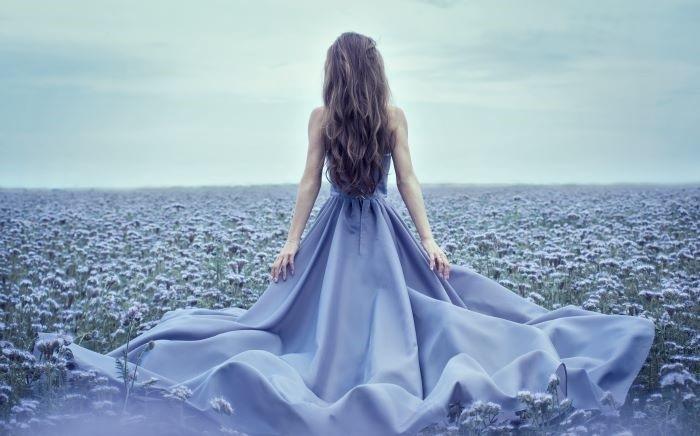 Mujer de espaldas con un vestido formal de color azul de seda