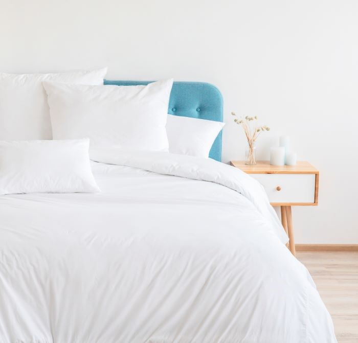 cama en dormitorio de leroy merlín con edredón y cojines