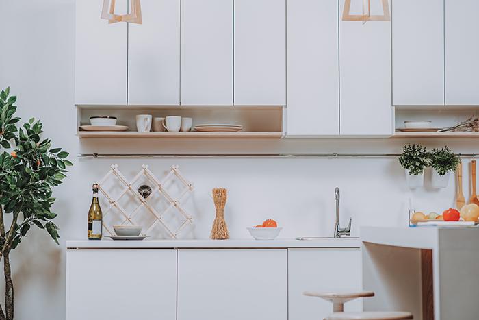 cocina pequeña con muebles blancos y armarios superiores con baldosas