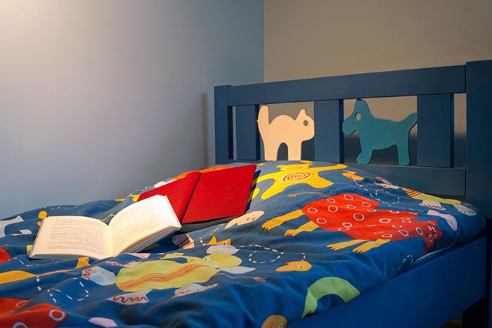 Cabecero de cama infantil en dormitorio con iluminación nocturna y dos libros encima de la cama
