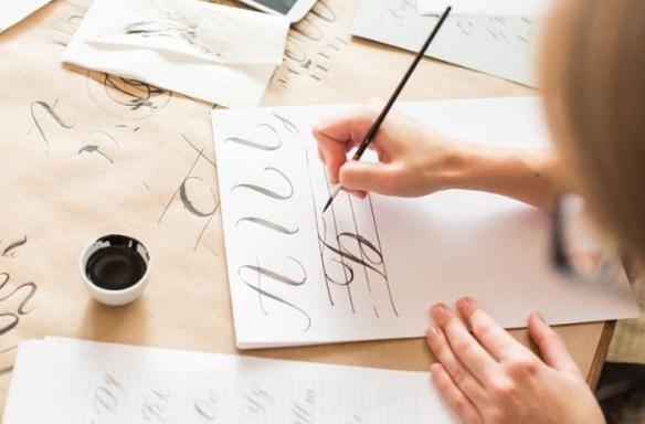 Escritura diseño caligrafía con tinta en papeles