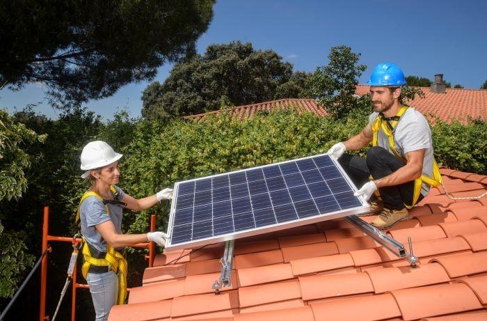 PAreja de profesionales instalando un panel solar en el tejado de una casa