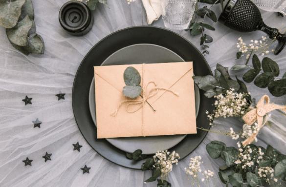 Invitación de boda encima de plato y mesa decorada