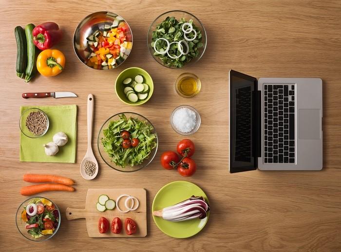 portátil junto a ingredientes para realizar una receta saludable