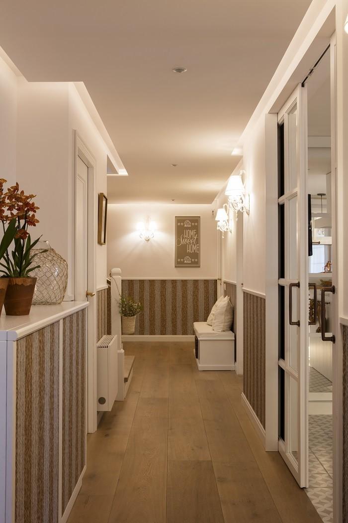 amplio pasillo o zona de paso con un banco y paredes blancas