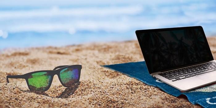 gafas de sol y portátil en la arena de la playa