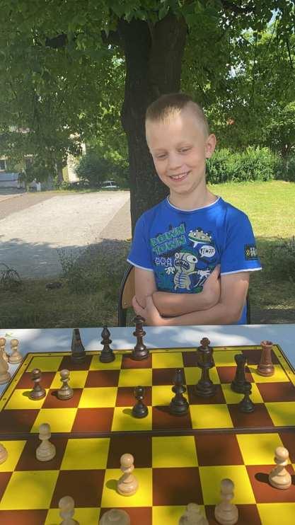 Zdjęcie przedstawia chłopca przy szachach