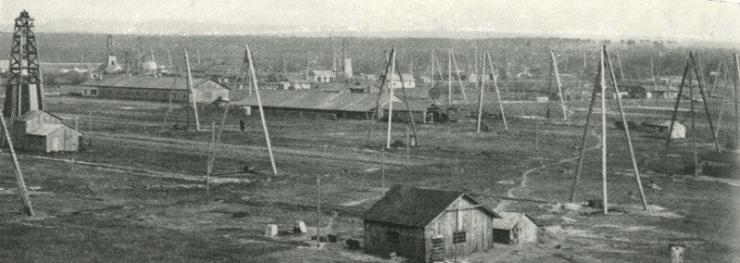 Panorama dolů na Nesytu s těžebními trojnožkami a strojními vrtnými soupravami, 20. léta. (zdroj:100 let průzkumu a těžby ropy a zemního plynu na jižní Moravě, Hornická Příbram 2013.
