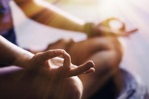 Closeup of woman's hands meditating indoors