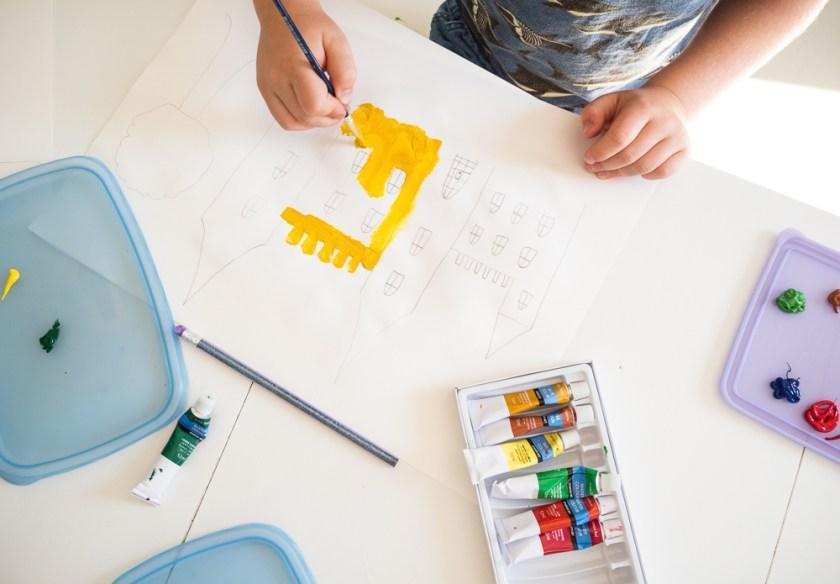 Kind-beim-Malen-einer-Burg-mit-Aquarellfarben