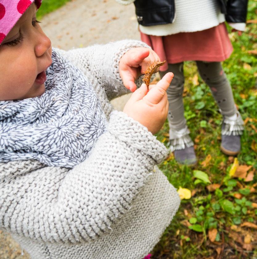 Herbstaktivitäten mit Kindern Mädchen hält Kastanie