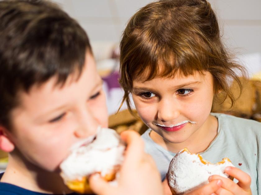 Krapfen backen mit Kindern_Junge und Mädchen essen Krapfen