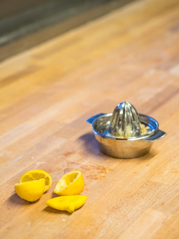 Krapfen backen mit Kindern - Zitronenhälften neben Zitronensaftpresse
