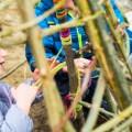 Weidentipi mit Kindern bauen_Kinder wickeln Wolle