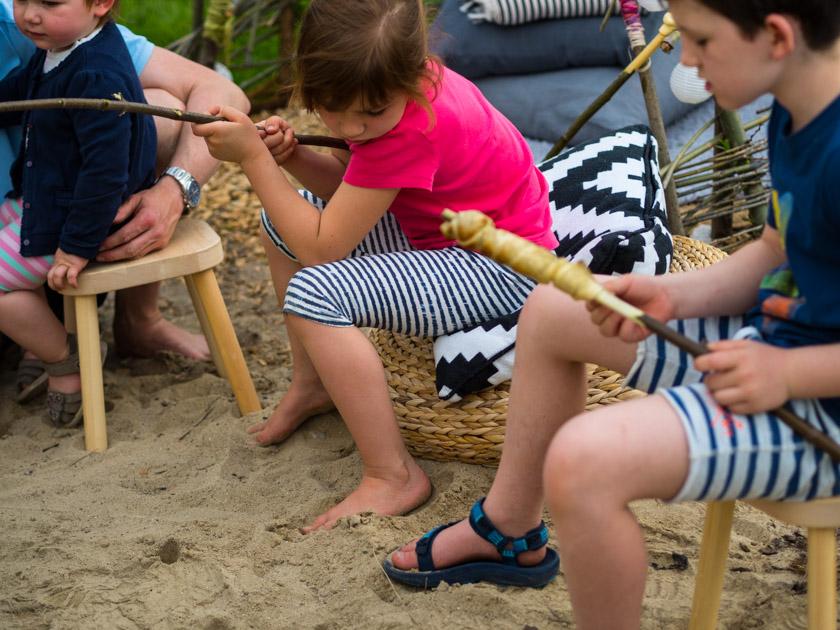 Weidentipi mit Kindern bauen_Kinder grillen Stockbrot