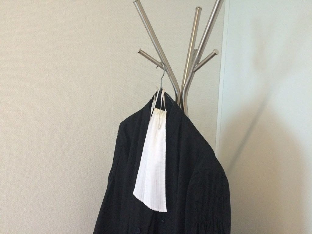 Black legal gown with collar hanging from metal hanger