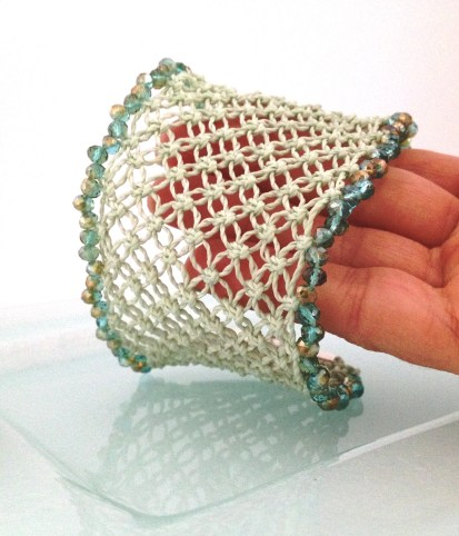 Bracciale a fascia realizzato a mano a macramè in una sfumatura pastello del Lucite green PantoneCuff bracelet handmade in macramé in a shade of pastel Lucite green Pantone.