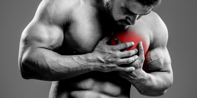 Bodybuilder holding chest with heart pain