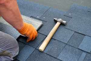 Contractor installing bitumen roof shingles using hammer in nails.