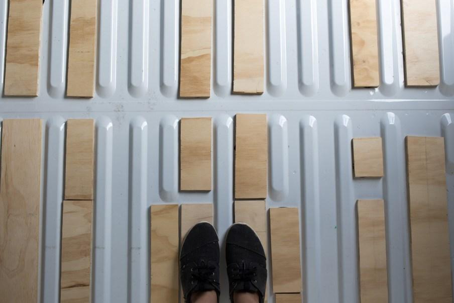 Standing on the strips of wood on the van floor