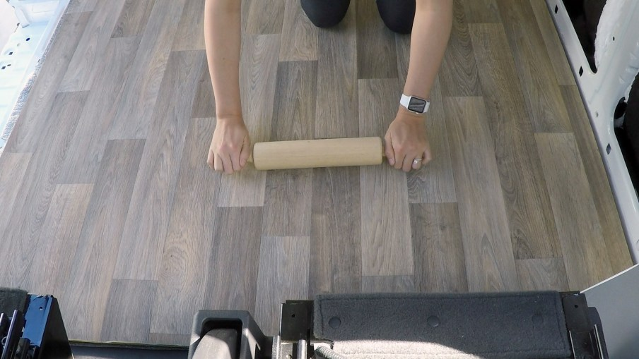 Using a rolling pin to remove air bubbles from the vinyl floor
