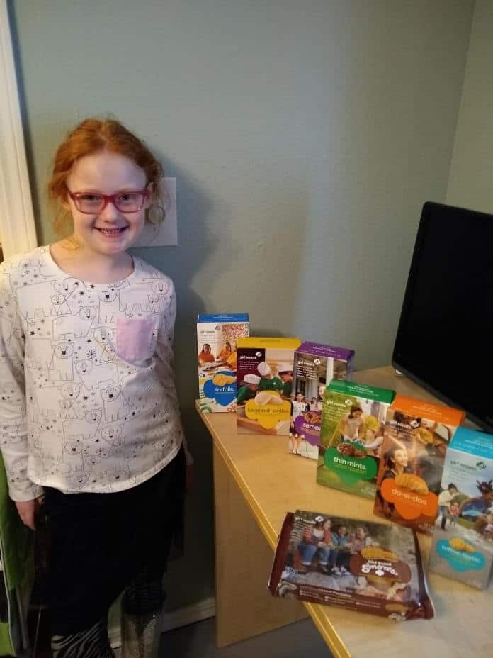 young girl scout standing next to a display of Girl Scout cookie boxes