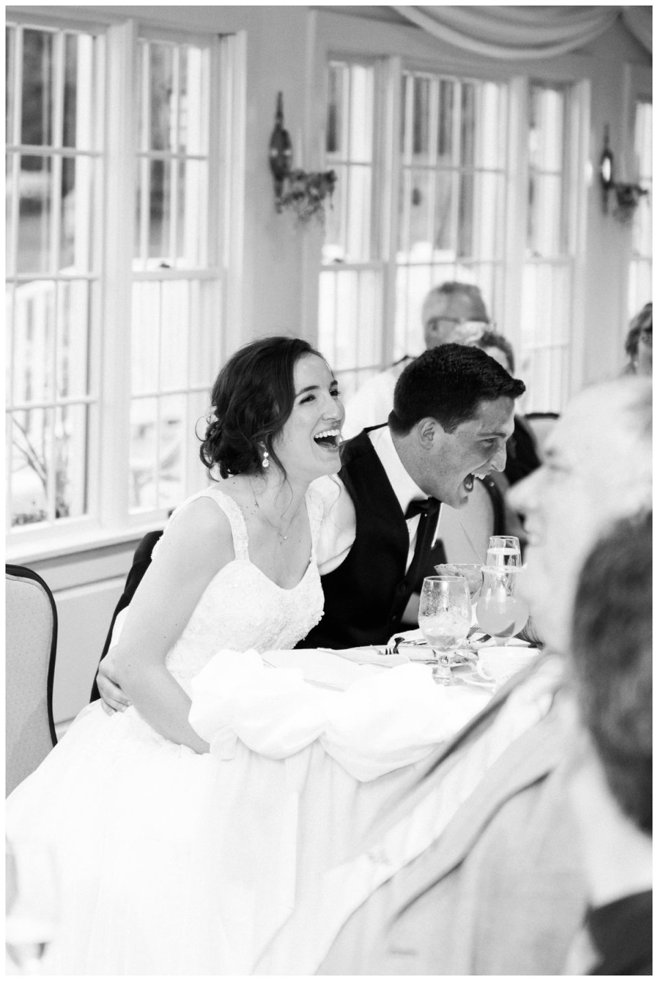 bride and groom laughing at sweetheart table