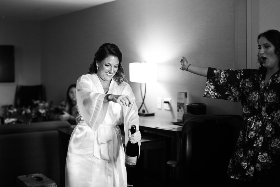 Bride popping champagne in bridal suite