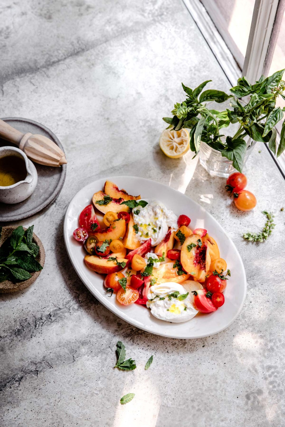 A quick and easy late summer salad of ripe peaches and tomatoes with creamy burrata and a sprinkling of fresh herbs. Top it all off with golden olive oil for a gluten free summer side dish.