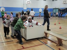 Notre Dame Principal Marlene Pelletier was participating in one of the sports at the Notre Dame Winter Olympics held Thursday. Adam Constantin, Alex Pellerin, Dylan Himschoot, Preston Landry, Lucas St. Martin and Ty Nordin help their principal make her way down the track.