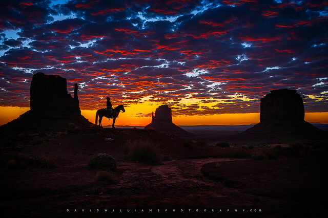 Navajo indian watching the sunrise on his horse at monument valley, arizona