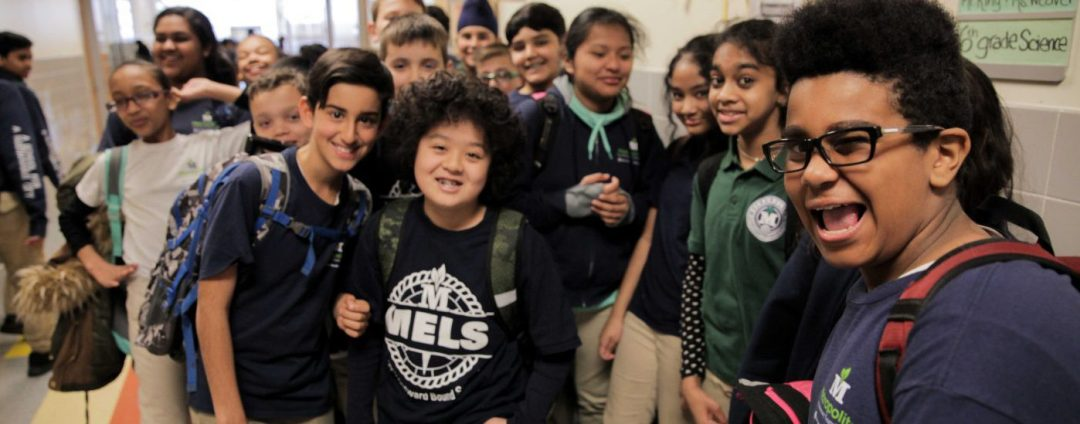 Mix of students smiling in school hallway