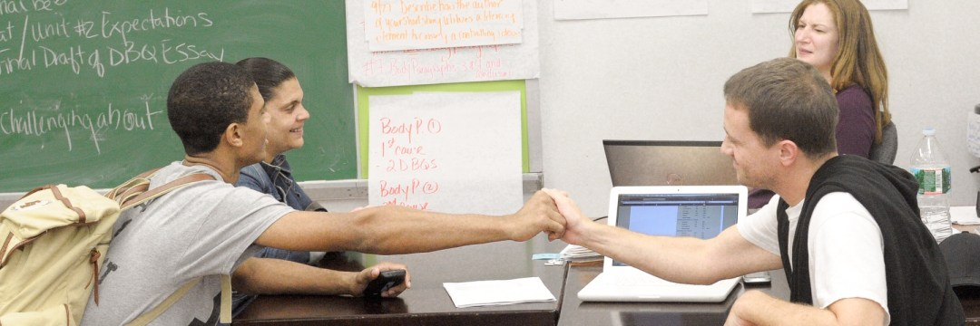 Teacher and student shaking hands following a successful parent teacher conference