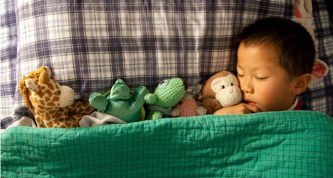 Child asleep in bed next to a row of stuffed animals.