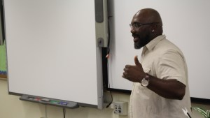 Community School Director Bruce Prescod is pictured leading a discussion at the front of a classroom.