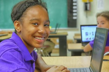 Girl in purple shirt leaning over an open laptop at a desk inside of a classroom.