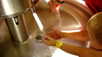 Child washing hands at a sink.