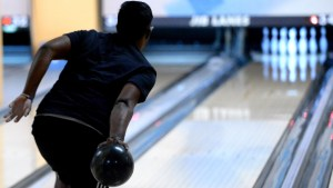 Shot of student as he prepares to launch a bowling ball down a lane.