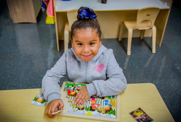 Kindergarener smiling at camera while playing with a puzzle