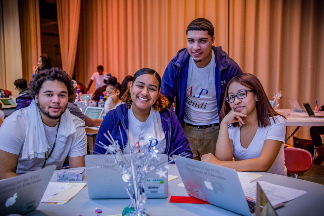 Four high school students around a table with laptops open and smiling towards the viewer.