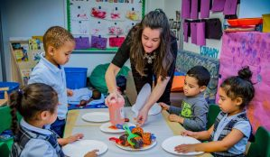 Teacher helping four students sitting at table with Playdoh