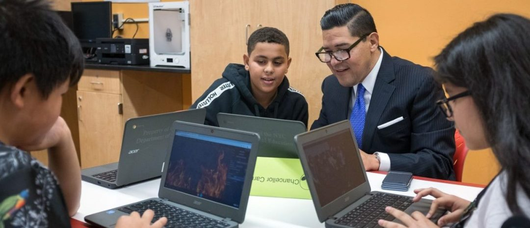 Chancellor Carranza observing a students work on his laptop