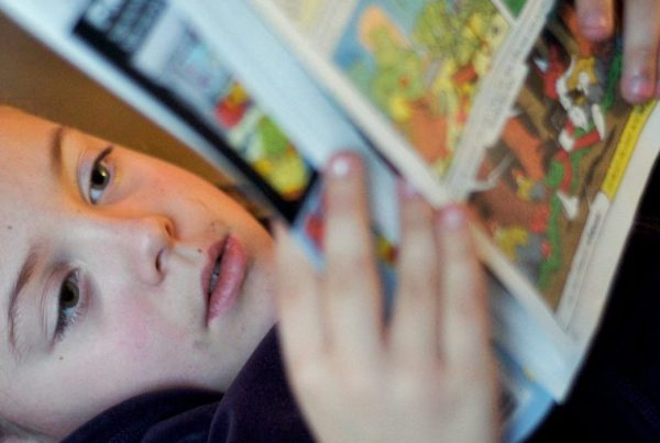 Child lying down while reading comic book