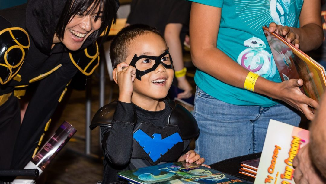 Child, with parent looking on, in costume waiting for comic book creator's autograph