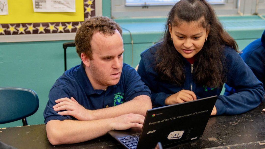 Ross Berman working alongside one of his students in front of a laptop