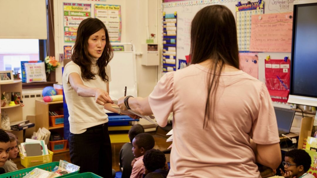 Annie Kim (left) hands lesson overview to teacher before starting her demo lesson