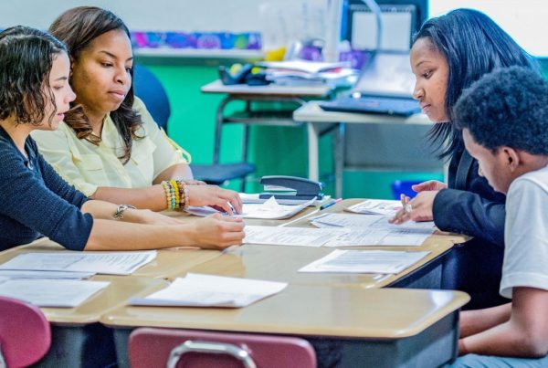 Teachers working with a parent and her child during a parent-teacher conference